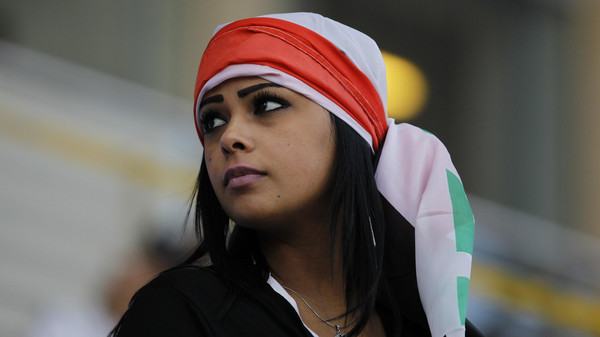 Fan wearing Iraqi flag on her head arrives to watch their Gulf Cup Tournament soccer match against Yemen at Khalifa Sports City in Isa Town