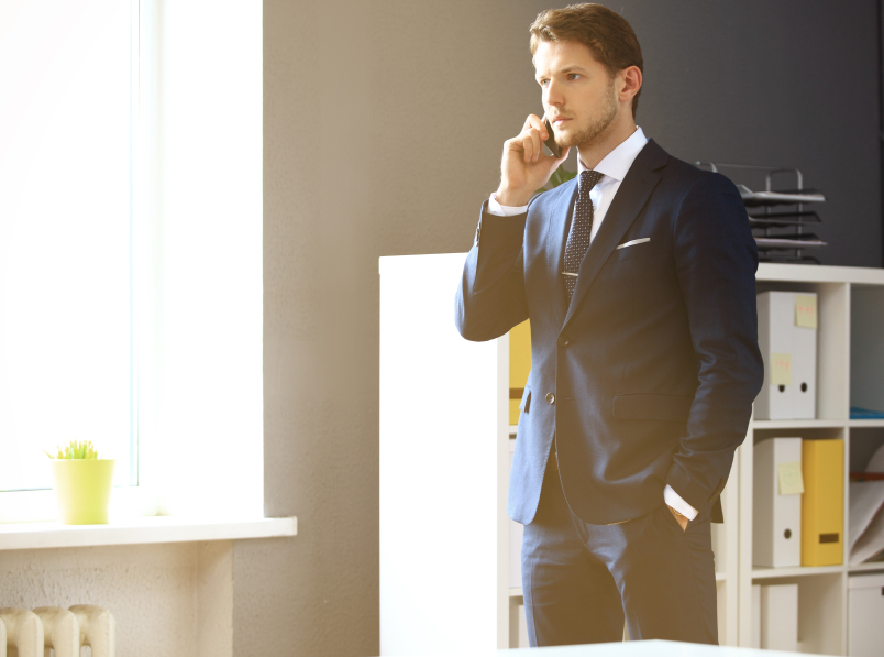 Handsome businessman in suit speaking on the phone in office